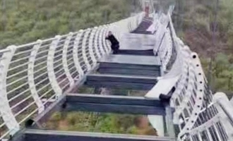 Tourist in China left dangling in thin air to die for, after string winds shatter glass bridge.